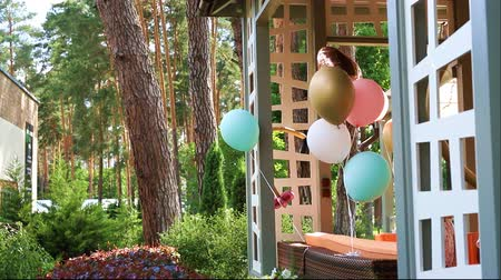 Bunch of different colorful helium air balloons playing on wind tied to wooden outdoor gazebo terrace as decoration for children bithday party. Anniversary celebration decor design