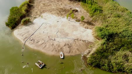 dragueur : Aerial drone view of custom-made dredger pump washing sand and deepening fairway at sandy silt island coast on river or lake shore