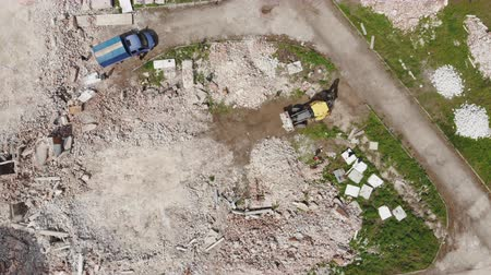 lebontották : Aerial drone view of old demolished industrial building. Pile of concrete and brick rubbish, debris, rubble and waste of destruction ruins of abandoned actory or plant. Heavy machinery work Stock mozgókép