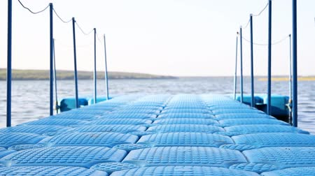 Blue floating plastic pontoon pier with rope railings rocking on waves at lake or river beach. Dock for small boats and people walkway