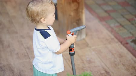 Cute adorable caucasian blond toddler boy having fun helping parents watering garden and lawn with hose and sprinkler at house backyard Vídeos
