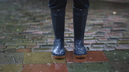 Person standing in dark blue rain boots on paved road at backyard,city street or park during heavy autumn rain. Moody scenic fall rainy weather forecast