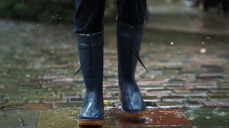 Person standing in dark blue rain boots and marching on place on paved road at backyard,city street or park during heavy autumn rain. Moody scenic fall rainy weather forecast