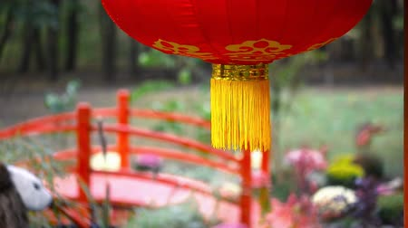 ahorcada : Traditional red chinese paper hanged lantern rocking on wind with red wooden bridge and asian landscaping design garden on background