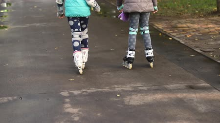 Two cute little caucasian girls having fun riding roller skates at city park by wet asphalt sidewalk after rain at autumn or spring . Young girlfriends having fun together outdoors