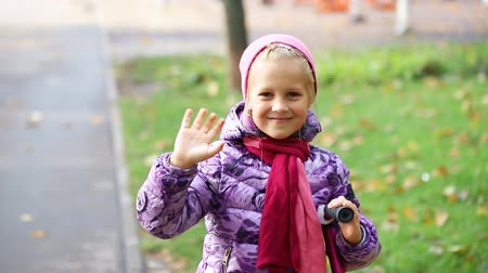 Cute adorable caucasian blond happy school girl smiling and waving hand in city park at warm autumn day. Cheerful child giving hello gesture playing outdoors