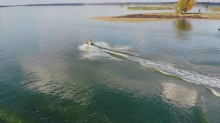 Aerial drone view of person having fun riding jet ski and making scenic stunts on emerald clear green sea or lake water. Extreme summer sport activities and travel. Holiday vacation adventure