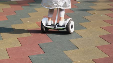 gyroscope : Close-up cute preschooler girl riding white hoberboard at children playground in city park outdoors