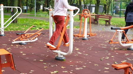 elliptical : Senior and youth people making sport exercises and training at public outdoor gym area at city park. Healthy lifestyle concept