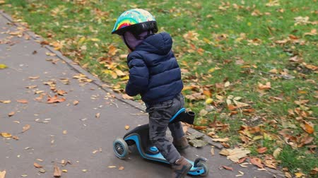mobilet : Little toddler boy riding scooter balance bike by asphalt walkway together with mother walking near path at city park at autumn outdoors.Small child having fun cycling fast at city street