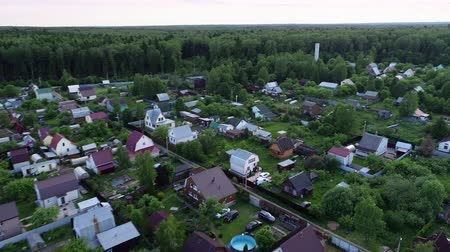 banliyö : 4k. Cinematic aerial footage. A beautiful little village or township in a green summer forest. The drone flies over the roofs of the houses.