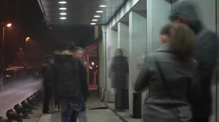 kuyruk : Waiting for Something; Time-lapse of people waiting for something at night in front of a building Stok Video