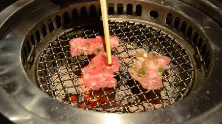 serpenyő : Slice sirloin on hot charcoal grill pan with a chopstick turning them Stock mozgókép