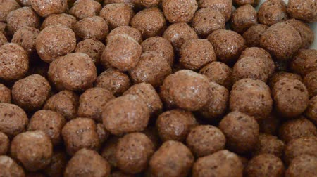biała czekolada : Pile of choco balls cereal pouring into white isolated background Wideo