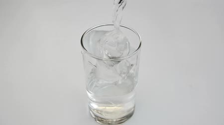 чистый : Pouring drinking water into a glass in white background