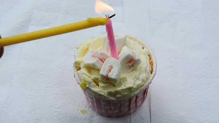 oŚwietlenie : A man is lighting a candle on a cupcake with marshmallow. Wideo