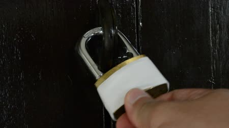 защелка : The man locks the door with his key quickly.