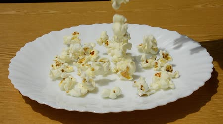попкорн : Salty popcorn is poured on a white dish.