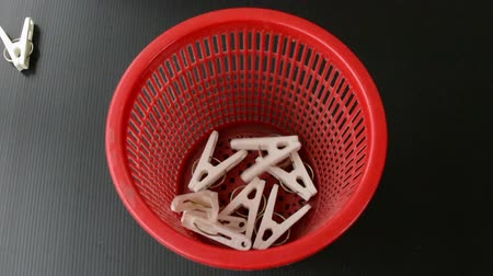 kept : White clothes-pegs are poured into a red basket on a black background.
