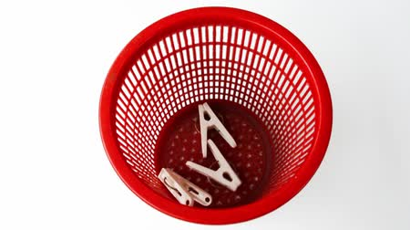 ubrania : White clothes-pegs are poured into a red basket on a white background