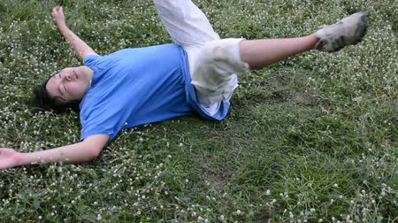 muži : An Asian guy is drop dead on the grassy ground, turning his face up