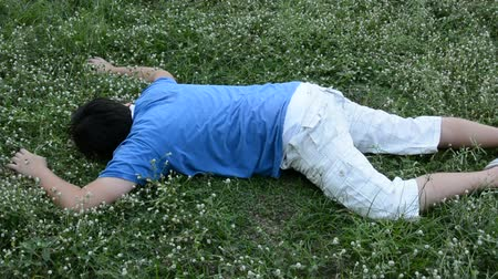 padající : An Asian guy is drop dead on the grassy ground and twitching
