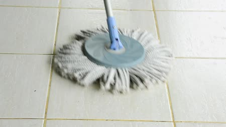 çini : A mop is used to clean a white tile floor