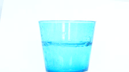 tisztaság : Pure drinking water turn green glass into blue color in white background. It it purify concept.