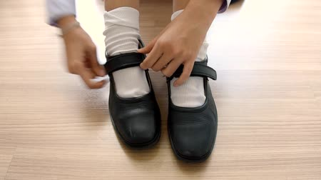 uniforme : Asian Thai schoolgirl student in high school uniform is wearing her black leather shoes in cute education fashion design on the wooden floor classroom