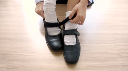 középiskola : Asian Thai schoolgirl student in high school uniform is wearing her black leather shoes in cute education fashion design on the wooden floor classroom