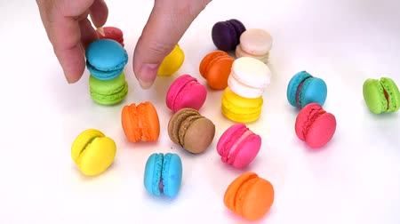 cakes : Closeup of a womans hand picking and aligning colorful macaron macaroon dessert food in fancy decoration on white isolated background on 1920x1080 HD quality video.