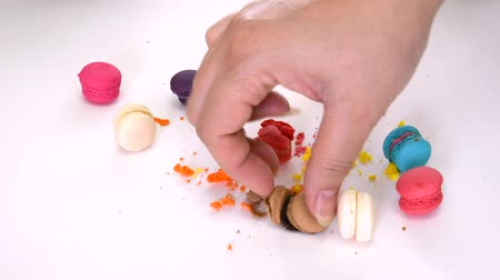 pastry : Closeup of a womans hand picking up messy colorful macaron macaroon candy dessert and its tiny bits which smash and squash on the floor on white isolated background on 1920x1080 HD quality video. Stock Footage