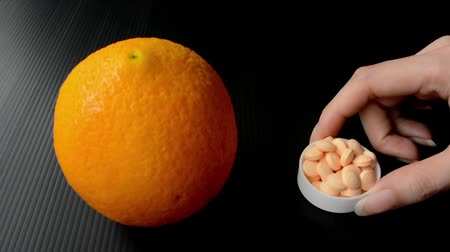 organic : An orange fruit is compared to the bowl of vitamin c supplements which both contain nutrition for health care (quality update) Stock Footage