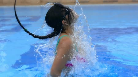 teen action : An Asian Thai girl is jumping from the water pool and swing her hair making a splash in HD