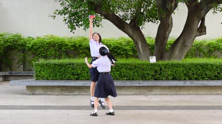 snatching : Cute Asian Thai high schoolgirls student couple in school uniform are having fun playing chasing and catching a doll with her student friend