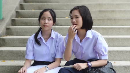 uniforme : Cute Asian Thai high schoolgirls student couple in school uniform sit on the stairway listening to a third person teacher or instructor with curious face expression with notebook on the lap.