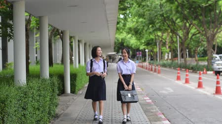 uniforme : Shallow depth of field changing to create blurry movement changing of cute Asian Thai high schoolgirls student couple in school uniform walking and chatting on the street together while walking to the camera.