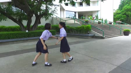 snatching : Cute Asian Thai high schoolgirls student couple in school uniform are having fun playing chasing and catching a doll with her student friend in a happy smile face expression Stock Footage