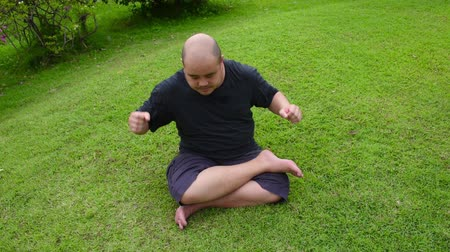 gritar : A fat bald head Asian Thai man is angry like a spoil child and then pounding wrigglingly tantrum aggressively on green grass in HD quality. Psychiatrist therapy is needed.