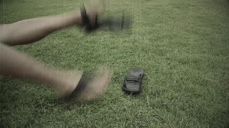 gritar : Old raw footage retro film grain of Asian man is flipping and kicking hitting his feet on the grass ground with madness or anger or has been abused. Body parts of feet kicking until the sandal shoes rip apart in aggression concept in HD.