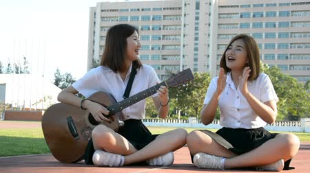 cantare : Cute Asian studente di college Thai paio ragazza in uniforme universitaria sedersi a cantare e suonare la chitarra divertirsi all'aperto con felice espressione. In studentessa amichevole e studente di college ragazza concetto di svago in HD.