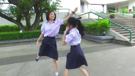 snatching : Cute Asian Thai high schoolgirls student couple in school uniform are having fun playing chasing and catching a doll with her student friend with action camera moving Stock Footage