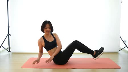 ruský : Pretty Thai Asian girl is doing Russian twist crunch in the air cardio workout exercise in white background in fitness show concept