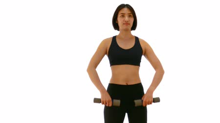 Pretty Thai Asian sportswoman is lifting dumbell in both arm standing upraise or V raise posture. Weight exercise cardio workout in white isolated background in fitness concept