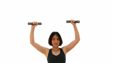 Pretty Thai Asian sportswoman is lifting dumbbell with shoulder press posture. Weight exercise cardio workout in half body white isolated background in fitness concept