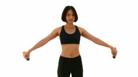 Pretty Thai Asian sportswoman is doing side dumbbell lateral raises posture. Weight exercise cardio workout in half body white isolated background in fitness concept