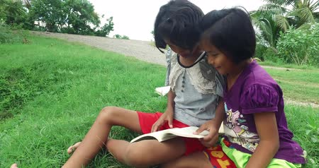 Cute Asian Thai girl children couple in casual clothes reading book and study in green field rural nature environment and find something exciting together. Happy young kindergarten or elementary schoolgirls learning in kid education concept in 4k Dostupné videozáznamy