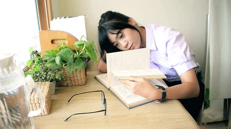 Cute Asian Thai high school girl in uniform study turning text book page with laziness on desk in her room with plants and window decoration in vintage retro or mojo color fashion style concept HD