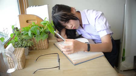 Cute Asian Thai high school girl in uniform doesnt understand her homework and spinning her pen while thinking on desk in private room in funny facial expression education concept HD