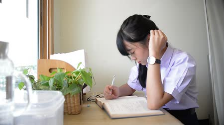 Cute Asian Thai high school girl in uniform writing studying and touching her hair on desk in private room doing homework with plants and window decoration in schoolgirl fashion and education concept HD